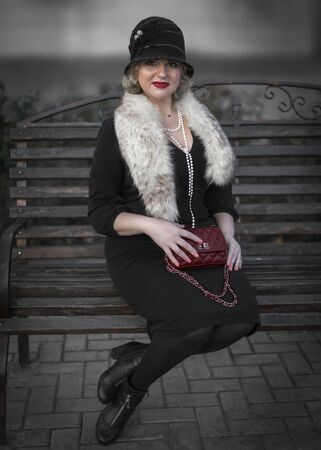 Pretty blonde woman dressed in retro style in fur boa, Cloche hat and holding a handbag on chain sitting on wooden bench on city street