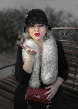 Pretty blonde woman dressed in retro style in fur boa, Cloche hat holding a handbag on chain sitting on wooden bench on city street and blowing a kiss
