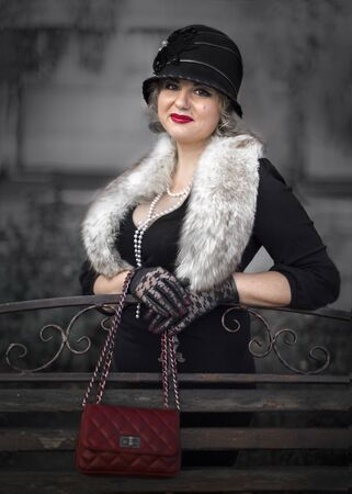 Pretty blonde woman dressed in the retro style in fur boa, Cloche hat and holding a handbag on chain standing on city street near a wooden bench
