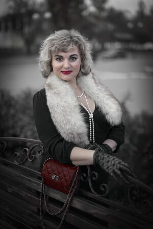 Pretty blonde woman dressed in the retro style in fur boa with a handbag on chain standing on city street near a wooden bench Reklamní fotografie