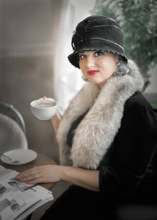 Beautiful woman wearing a hat Cloche sitting at a table in a coffee shop with a magazine and drinking coffee drink. Cosplay