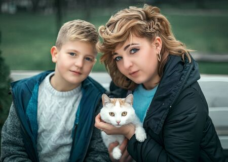 Family portrait young pretty mother holding a cat and teenager son sitting next to his mam and looking at camera in city park