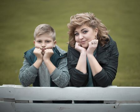 Family portrait young pretty mother and teenager son looking at camera in city park Reklamní fotografie