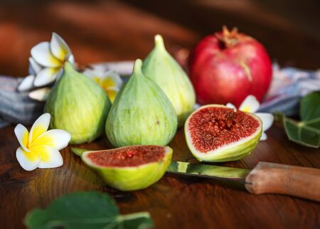Fresh whole and cut fruits figs, pomegranate and exotic plumeria flowers on wooden table background. Still life. Reklamní fotografie