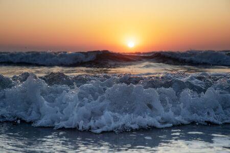 Waves of the Mediterranean Sea with sea foam and spray. Beautiful sea on sunset background. Sundown. Seascape. Running wave