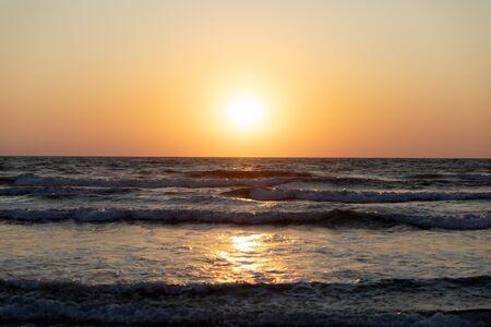 Waves of the Mediterranean Sea with sea foam and spray. Beautiful sea on sunset background. Sundown. Seascape