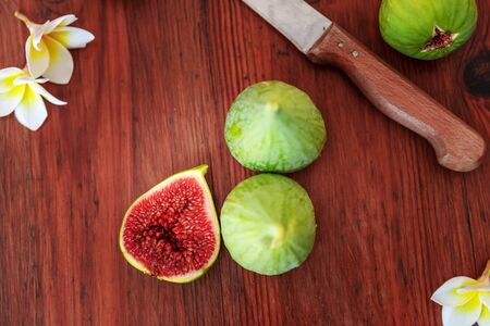 Closeup Fresh whole and cut fruits figs and exotic plumeria flowers on wooden table background with kitchen knife. Still life