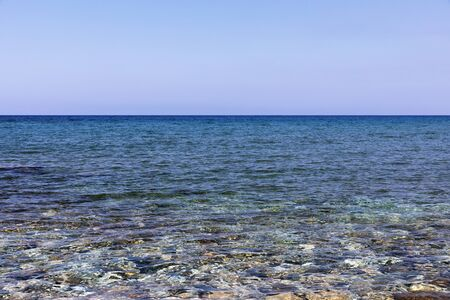 Mediterranean Sea in Northern Cyprus. Summer seashore with transparent blue water and stones background. Seascape. Skyline