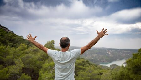 An aged happy man standing on top of a mountain with his arms outstretched. Beautiful view of the mountains and sky from the back of a man. The concept of freedom and happiness
