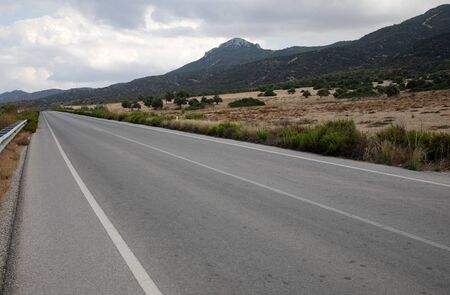 Road in Northern Cyprus. Landscape with road stretches into the distance against the backdrop of mountains.