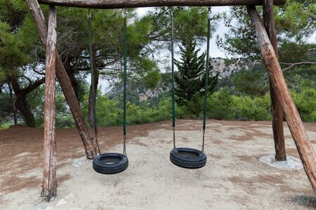 Two tire tire swings on trees. Beautiful North Cyprus mountain landscape.
