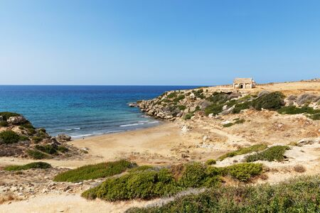 Mediterranean Sea in Northern Cyprus. The ruins of an ancient building on the island. Summer seashore with transparent blue water. Seascape. Skyline. Beauty of the planet