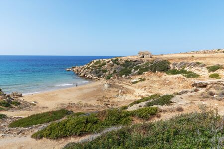 Mediterranean Sea in Northern Cyprus. The ruins of an ancient building on the island. Summer seashore with transparent blue water. Seascape