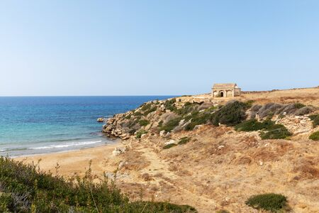 Mediterranean Sea in Northern Cyprus. The ruins of an ancient building on the island. Summer seashore with transparent blue water. Seascape. Skyline.