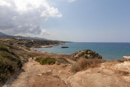 Mediterranean Sea in Northern Cyprus. The ruins of an ancient building on the island. Summer seashore with transparent blue water. Seascape. Skyline with clouds. Reklamní fotografie