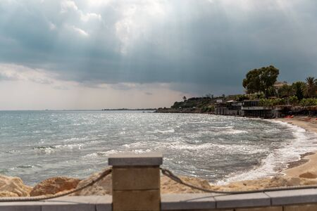 Mediterranean Sea in Northern Cyprus. Summer seashore with transparent blue water sun rays in the clouds. Seascape. Skyline
