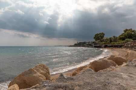 Mediterranean Sea in Northern Cyprus. Summer seashore with transparent blue water sun rays in the clouds. Coastline.
