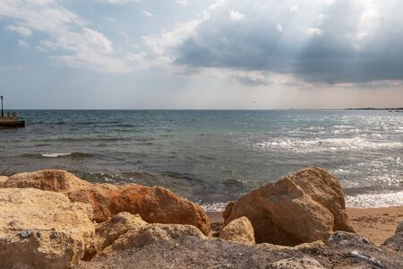 Mediterranean Sea in Northern Cyprus. Summer stone seashore with transparent blue water sun rays in the clouds. Seascape. Storm clouds with sunbeams. Reklamní fotografie