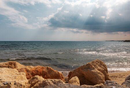 Mediterranean Sea in Northern Cyprus. Summer seashore with transparent blue water sun rays in rain clouds. Seascape. Skyline