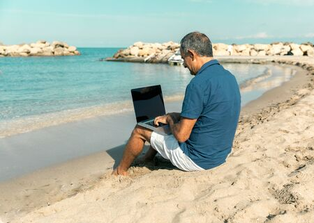 Adult male of mediterranean race using laptop while sitting on the sea beach. Freedom and travel concept.