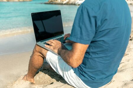 Adult person typing on laptop keyboard sitting on sandy sea beach. Freedom and travel concept.