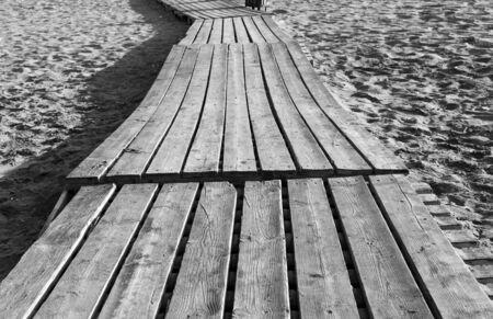 Old wooden flooring on a sandy beach. Summer black white background