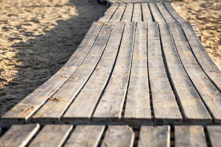 Old wooden flooring on a sandy beach. Summer background Reklamní fotografie