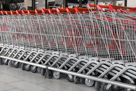 A long row of shopping trolleys or carts outside of a large supermarket