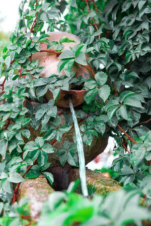 Decorative garden waterfall. Water jet pouring from garden jug.