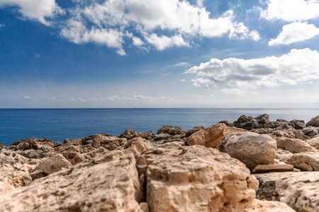 Mediterranean Sea in Northern Cyprus. Summer rocky coast, transparent calm blue water and white clouds on blue sky Reklamní fotografie