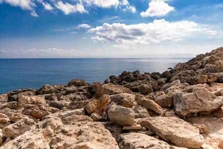 Mediterranean Sea in Northern Cyprus. Summer rocky coast, transparent calm blue water and white clouds on blue sky. Seascape. Skyline Reklamní fotografie
