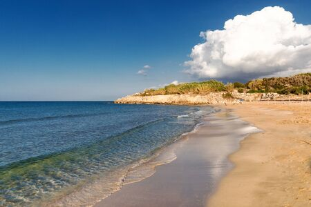 Mediterranean Sea in Northern Cyprus. Summer sandy coast, transparent calm blue water and white clouds on blue sky. Seascape. Skyline