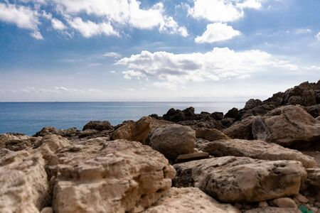 Mediterranean Sea in Northern Cyprus. Summer rocky coast, transparent calm blue water and white clouds on blue sky. Seascape