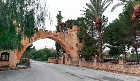 The road leading under a beautiful brick arch with columns. Northern Cyprus local attraction.