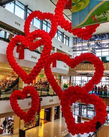 Cyprus - February, 2020: Valentines day decor red balloons in the shape of hearts in shopping mall hanging from the ceiling. Love Day Celebration. Shoppers in a store