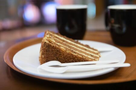 Two Coffee cups, plate with carrot cake or pie, disposable plastic knife, fork and spoon on a round tray on a table in a cafe in the evening or at night