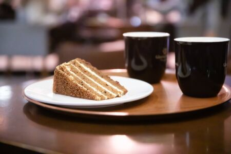 Two Coffee cups and a plate with carrot cake or pie on on round tray on table in cafe in the evening or night.