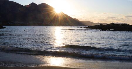 Beautiful sunset on the sea with splashing waves. Sunlight is reflected in the water. Seascape on the island of Cyprus. Sun Rays Over Kyrenia Mountains. 4k video 4096X2160