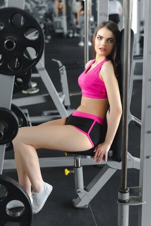 Young pretty sexy female sitting or resting in gym. Heathy lifestyle, sport conception. Banque d'images
