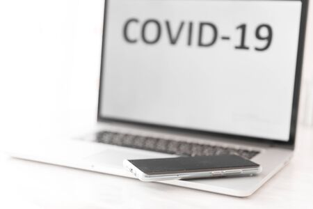 Computer screen with the inscription Covid-19 and a smartphone lying on the keyboard. World coronavirus Pandemic 2020. Background with copyspace.