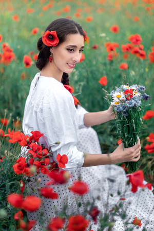 Portrait of a pretty young woman on the background of a blooming poppy field. Ukrainian woman sitting with a bouquet of wildflowers