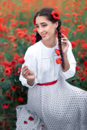 Portrait of a pretty young woman on the background of a blooming poppy field. Smiling Ukrainian woman sitting and holding a poppy flower Stok Fotoğraf