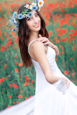 Portrait of a pretty young happy smiling woman wearing a wreath of wildflowers on the background of a blooming poppy field.