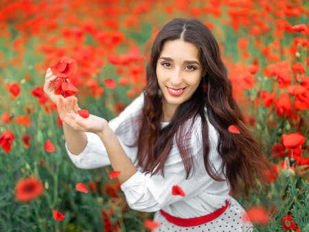 Young pretty girl Slavic or Ukrainian posing in folk dress on a flowering poppy field. Female holding poppy flowers with falling petals.