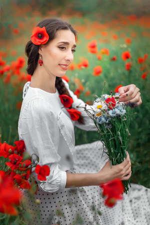 Young pretty girl Slavic or Ukrainian posing in folk dress on a flowering poppy field. Female holding a bouquet of wildflowers.