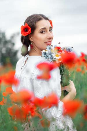 Young pretty girl Slavic or Ukrainian posing in folk dress on a flowering poppy field.