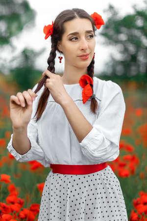 Young pretty girl Slavic or Ukrainian posing in folk dress on a flowering poppy field. Female weaving braid.