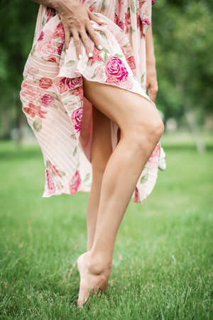 Young pretty woman in summer dress walking on meadow on green grass. The girl lifted the hem of her dress showing her beautiful legs