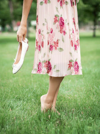 Young pretty woman in summer dress walking on meadow on green grass. A young girl holds white ballet shoes in her hands. Stok Fotoğraf