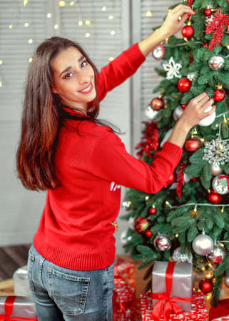 Happy young brunette female decorating christmas tree. Girl holding a christmas ball in her hands hanging on the tree